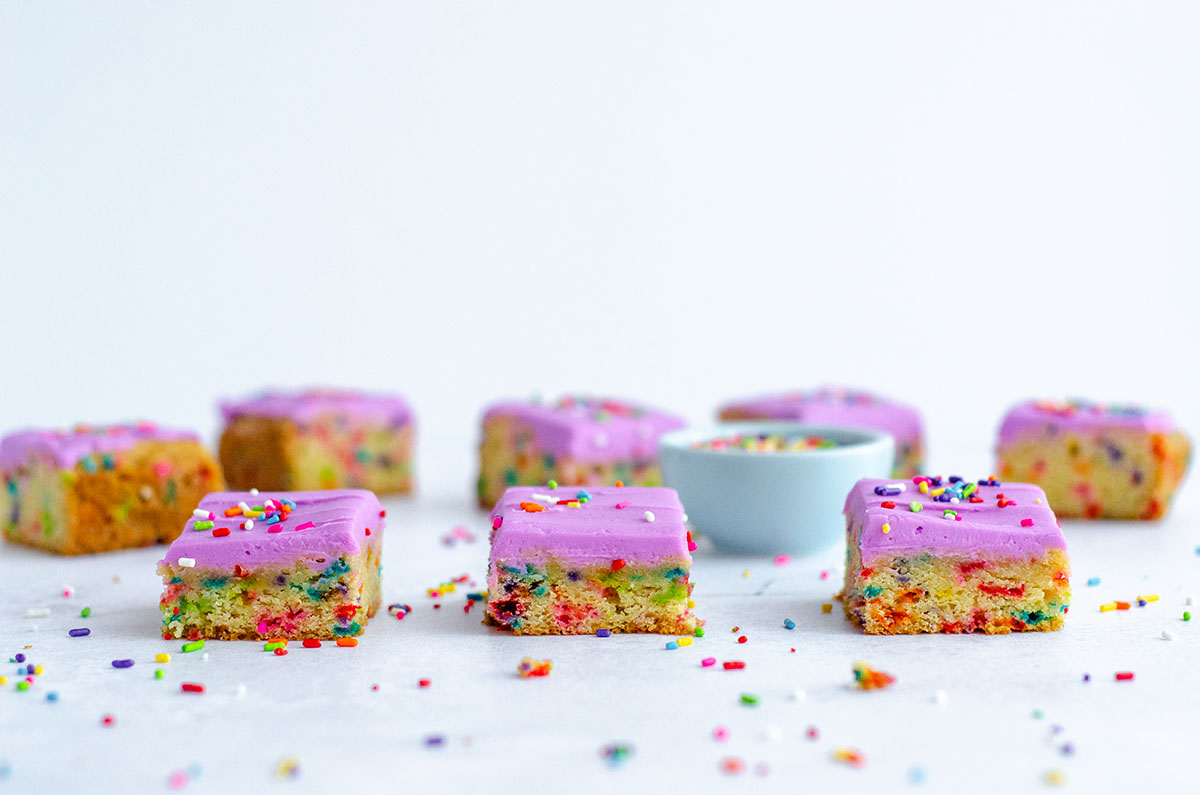 sugar cookie bars on a surface with sprinkles all around