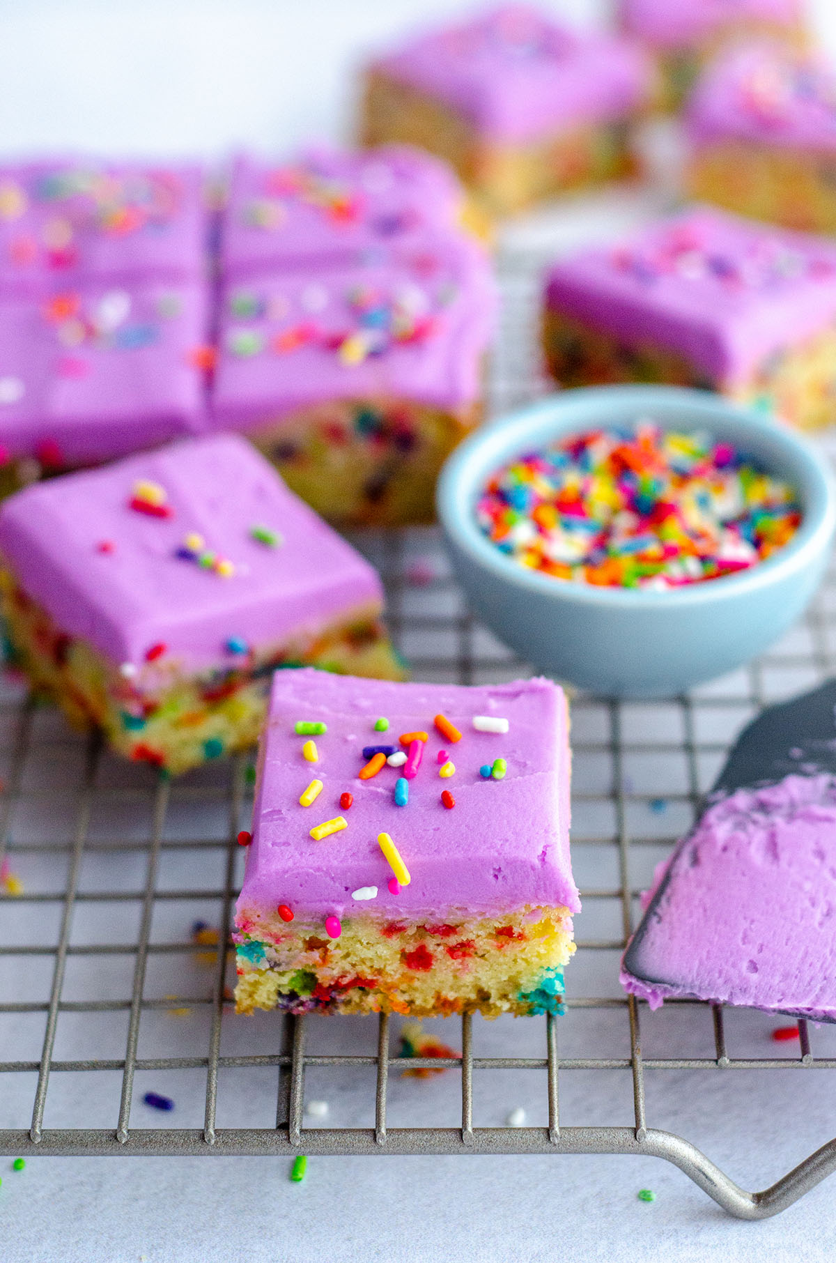 Soft and buttery sugar cookies in easy-to-serve bar form. Top with a colorful buttercream and rainbow sprinkles for an extra pop of color!