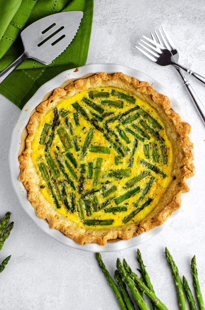 aerial photo of asparagus quiche in a pie plate with forks and a server around it