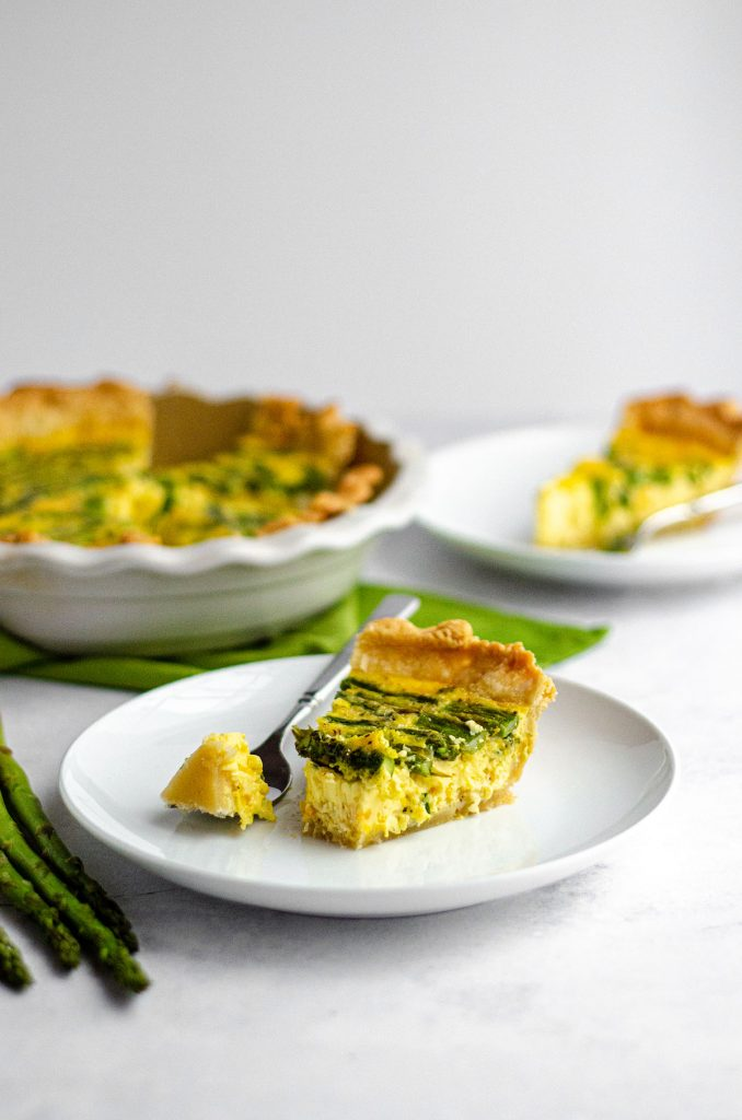 slice of asparagus quiche on a white plate with a fork and a bite taken out of the slice