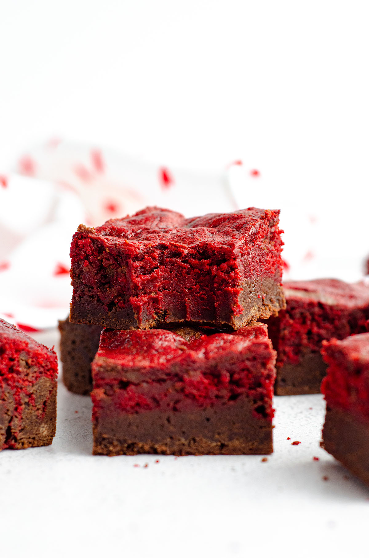 red velvet brownie with a bite taken out of it stacked on top of other red velvet brownies
