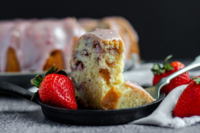 strawberry bundt cake sitting on a plate with a forkful taken out of it