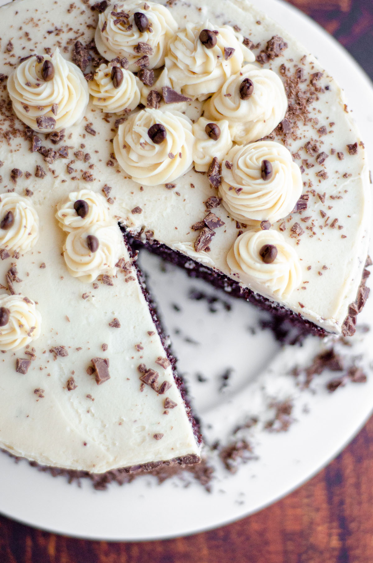 aerial photo of mocha cake with coffee buttercream on a plate with a slice taken out of it