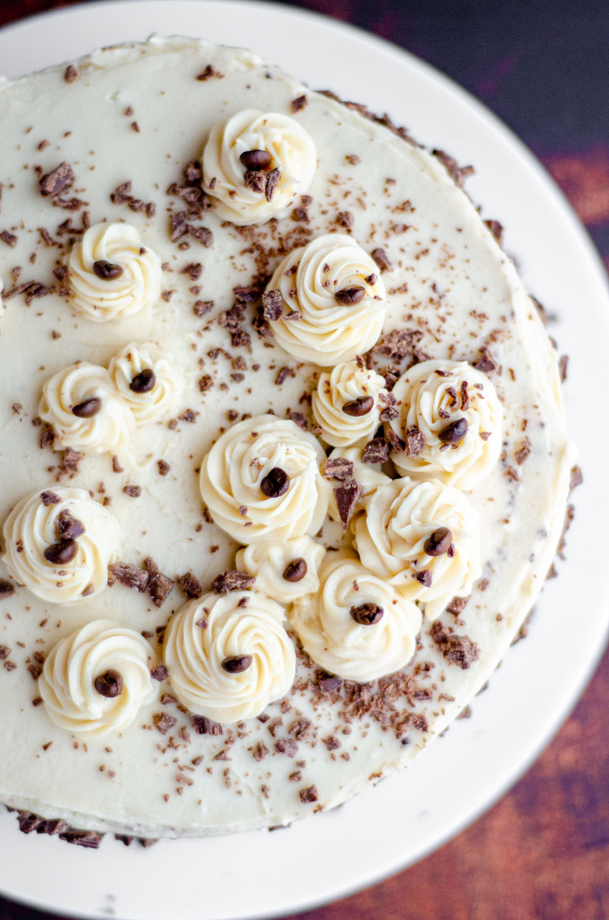 aerial photo of mocha cake with coffee buttercream decorated with chunks of chocolate and coffee beans