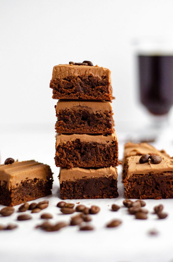 stack of coffee brownies with mocha frosting and a cup of coffee in the background