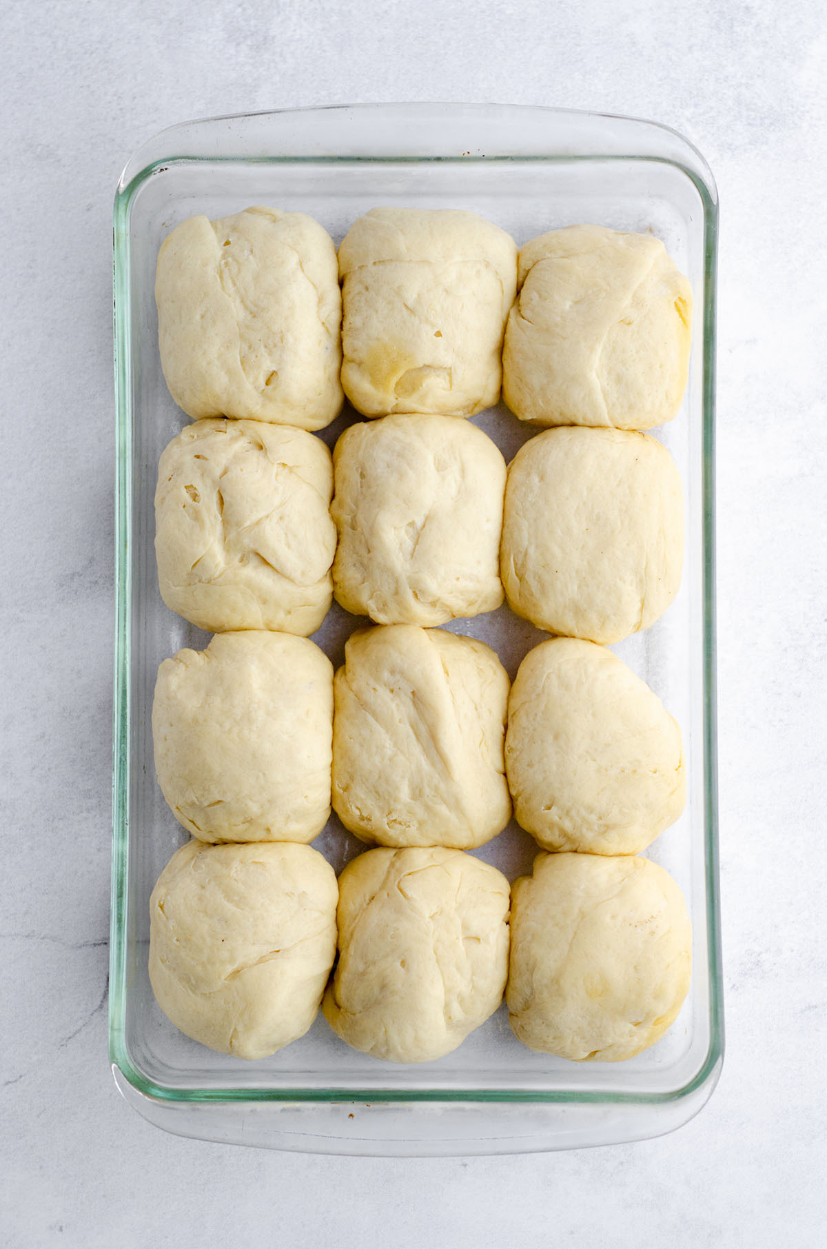 easy yeast roll dough in a glass baking dish ready to rise