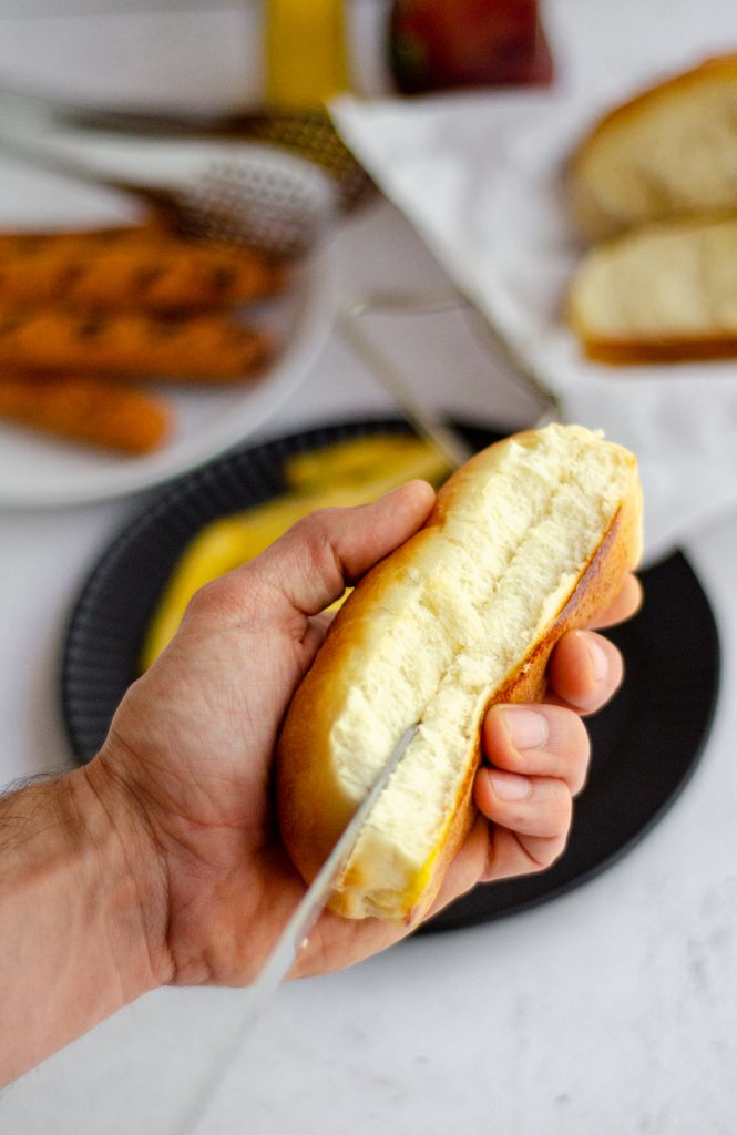a hand holding a homemade hot dog bun and cutting it open with a knife