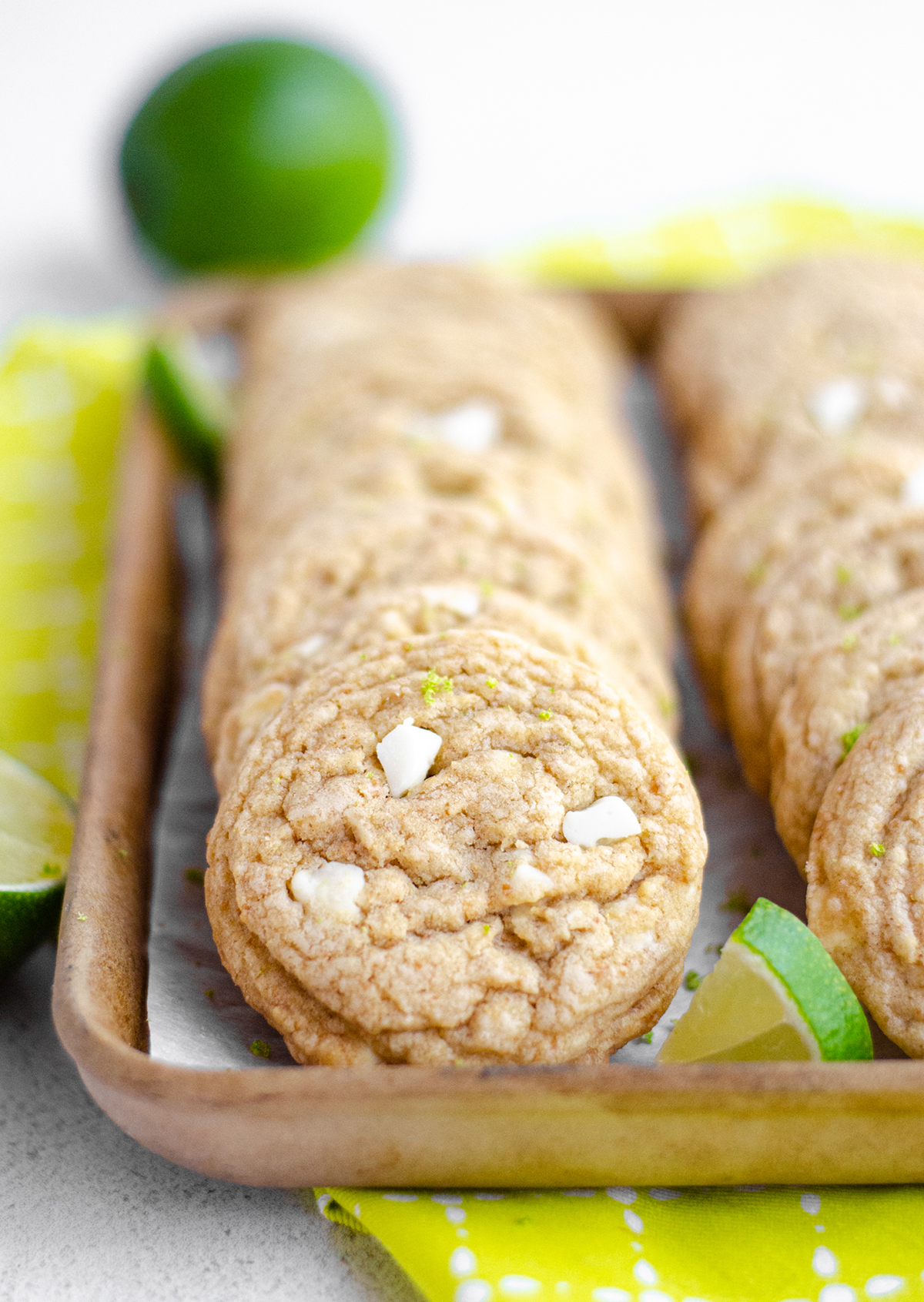 key lime cookies in a serving tray with lime slices scattered around them