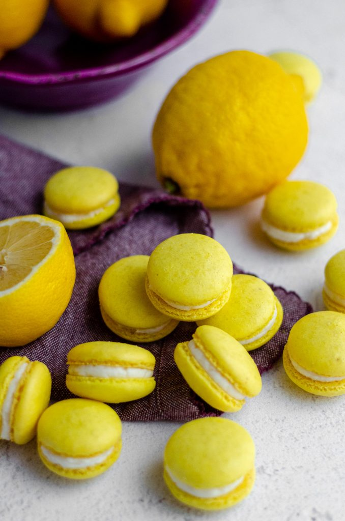 lemon macarons in a group on a purple kitchen towel