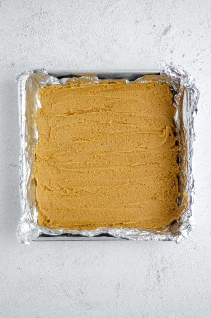 aerial photo of the peanut butter cookie base of brownies in a foil lined pan