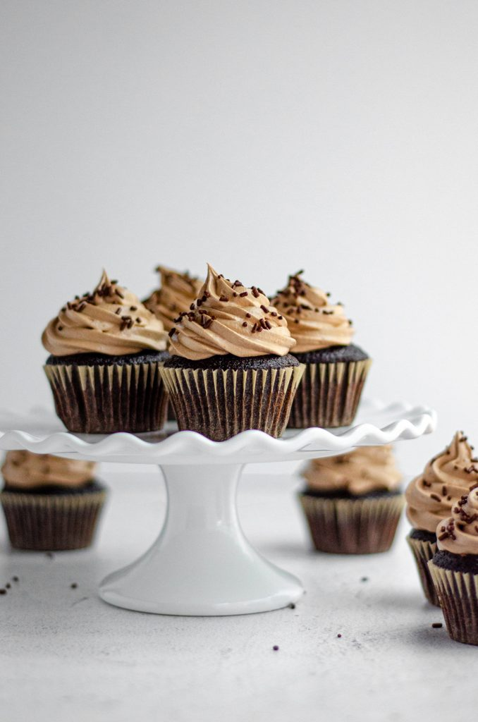 chocolate cupcakes with chocolate swiss meringue buttercream sitting on a white fluted cake stand