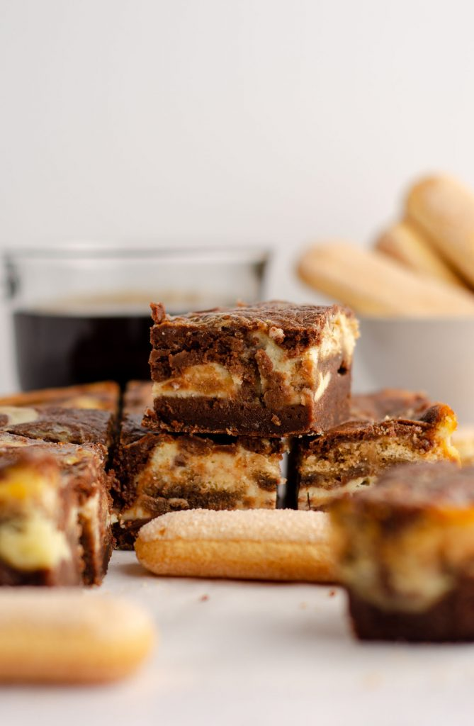 stack of tiramisu brownies with a cup of coffee and ladyfingers in the background