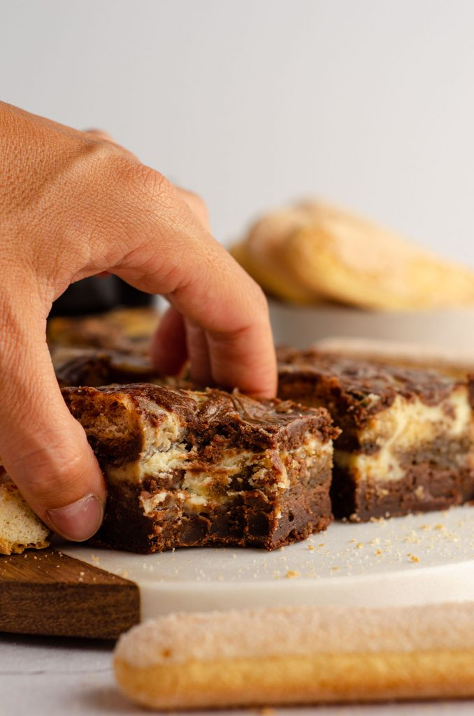a hand grabbing a tiramisu brownie from a platter with a bite taken out of it