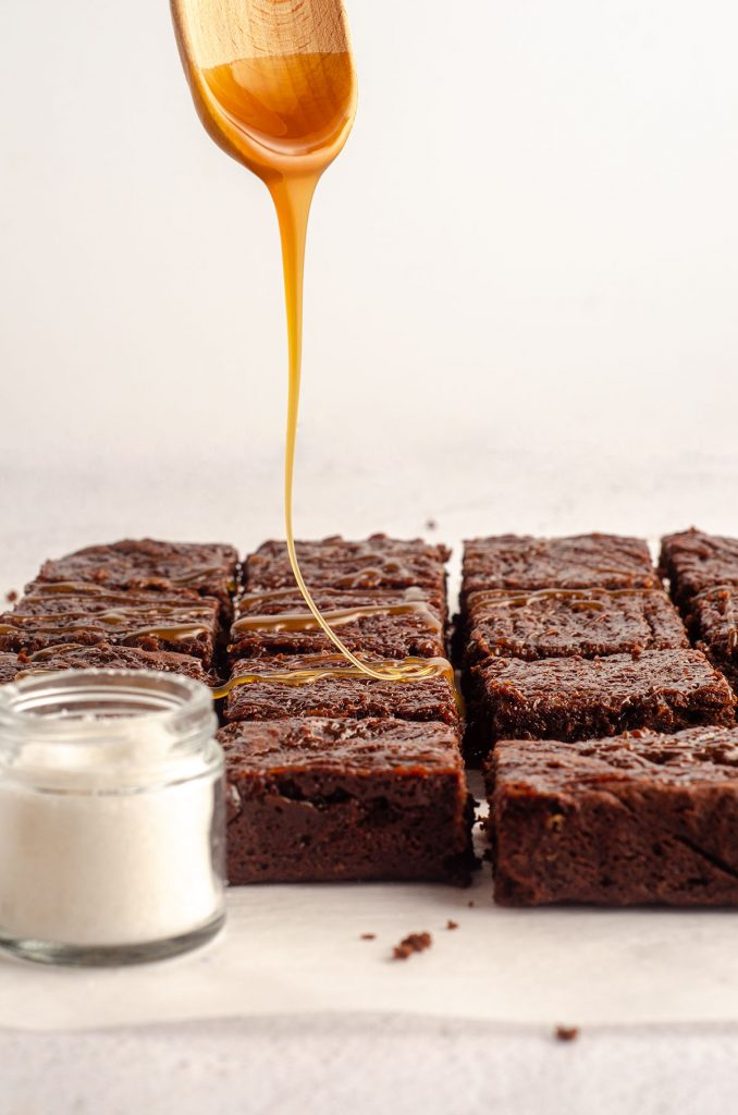 wooden spoon dripping caramel sauce onto salted caramel brownies