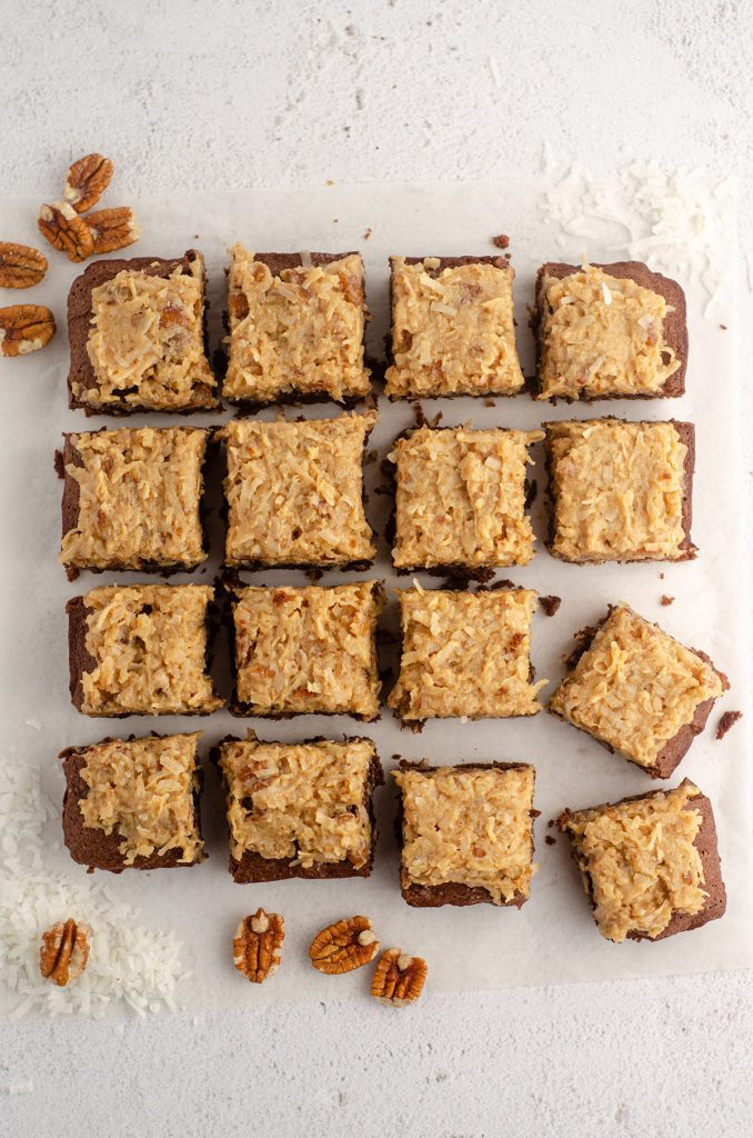 aerial photo of german chocolate brownies cut into 16 bars and scattered around with pecans and shredded coconut