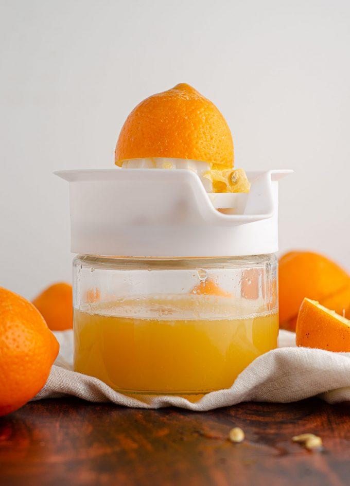 meyer lemon half sitting on top of a citrus juicer filled with meyer lemon juice