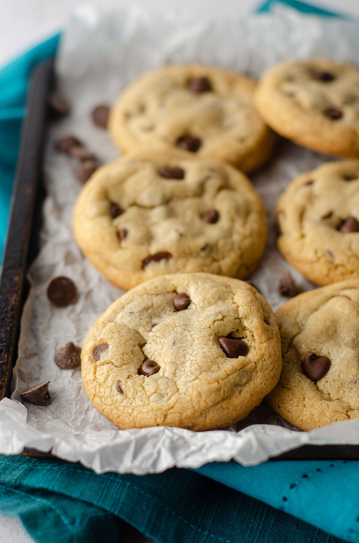 small batch of 6 chocolate chip cookies sitting on parchment paper on a baking sheet