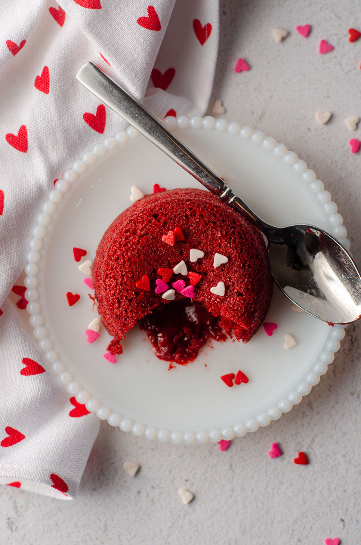 aerial photo of red velvet lava cake sitting on a white plate with heart sprinkles on top of it