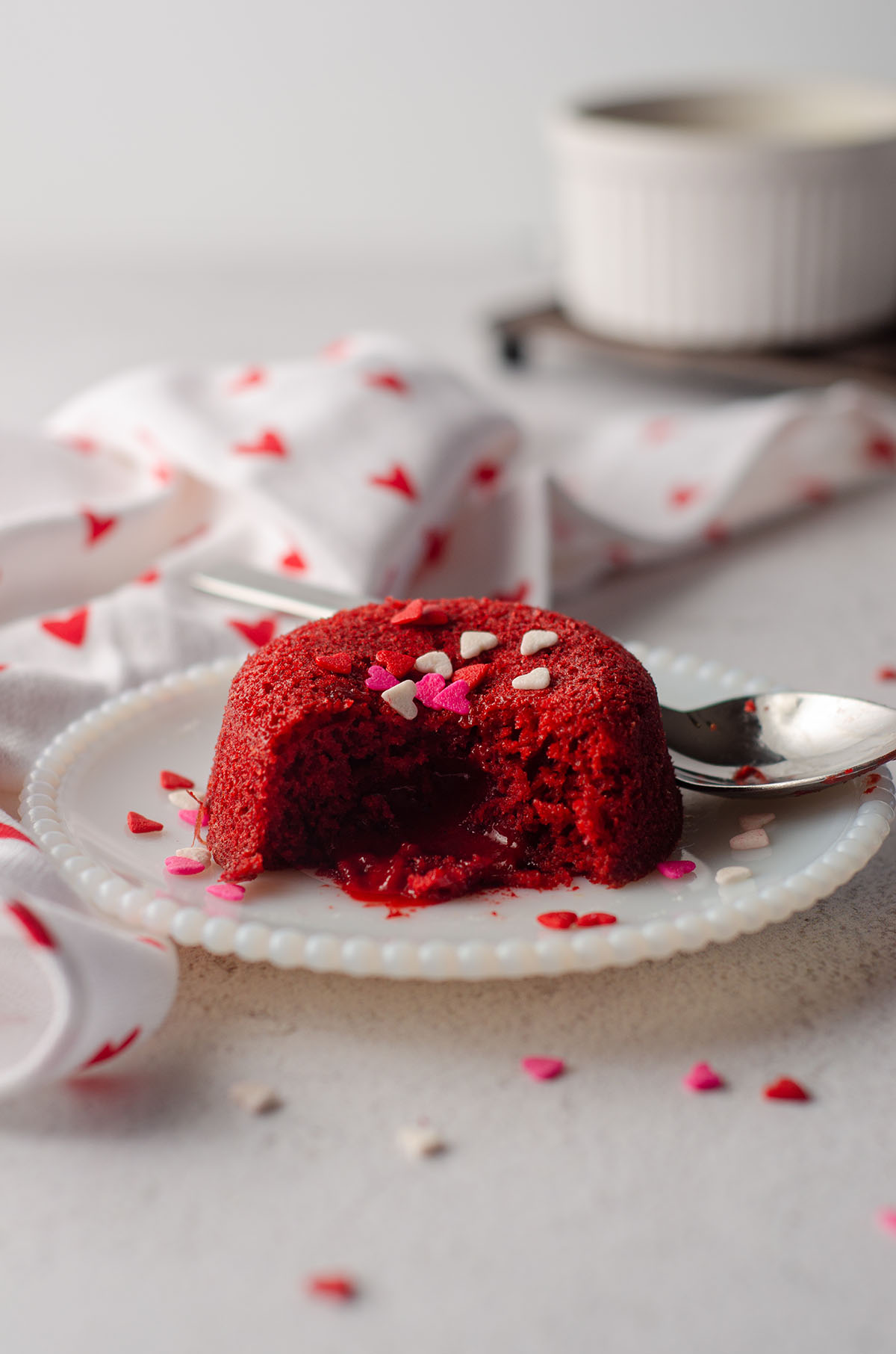 red velvet lava cake sitting on a white plate with heart sprinkles on top of it