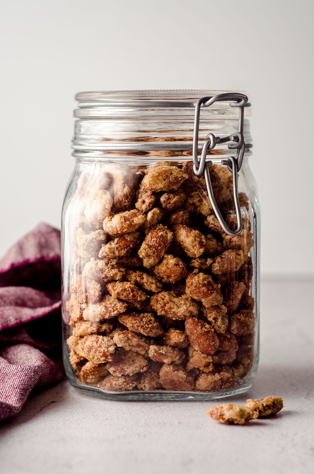 candied almonds in a jar with a plum colored kitchen towel next to it and almonds in the foreground