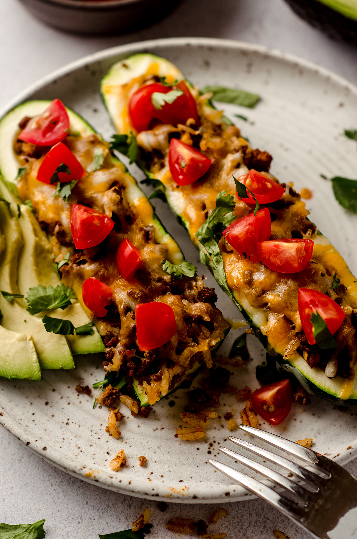 taco zucchini boats on a plate with a bite taken out of one