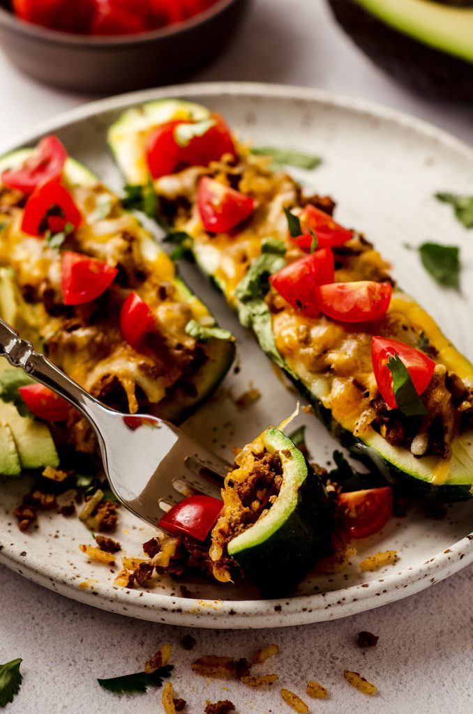 taco zucchini boats on a plate with a fork holding a bite