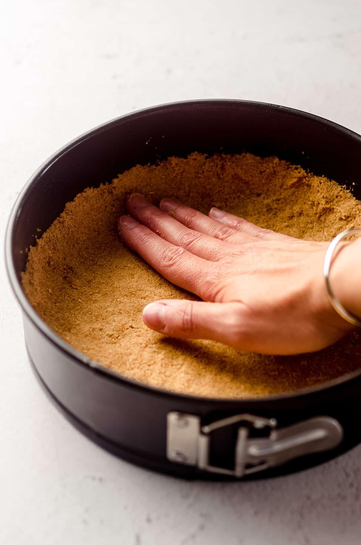 hand pressing a graham cracker crust into the bottom of a springform pan