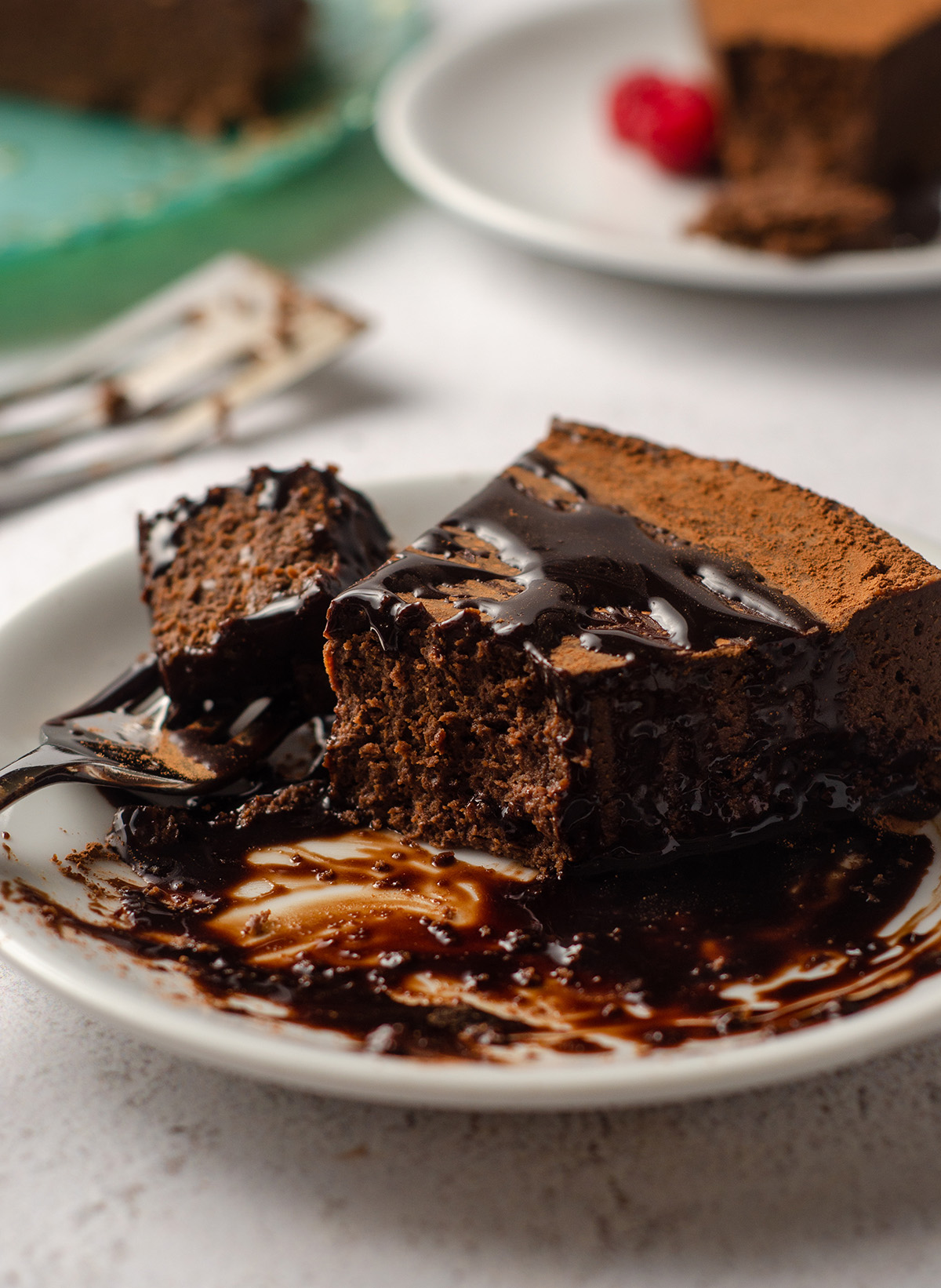 a slice of gluten free dairy free chocolate cake with chocolate syrup on it