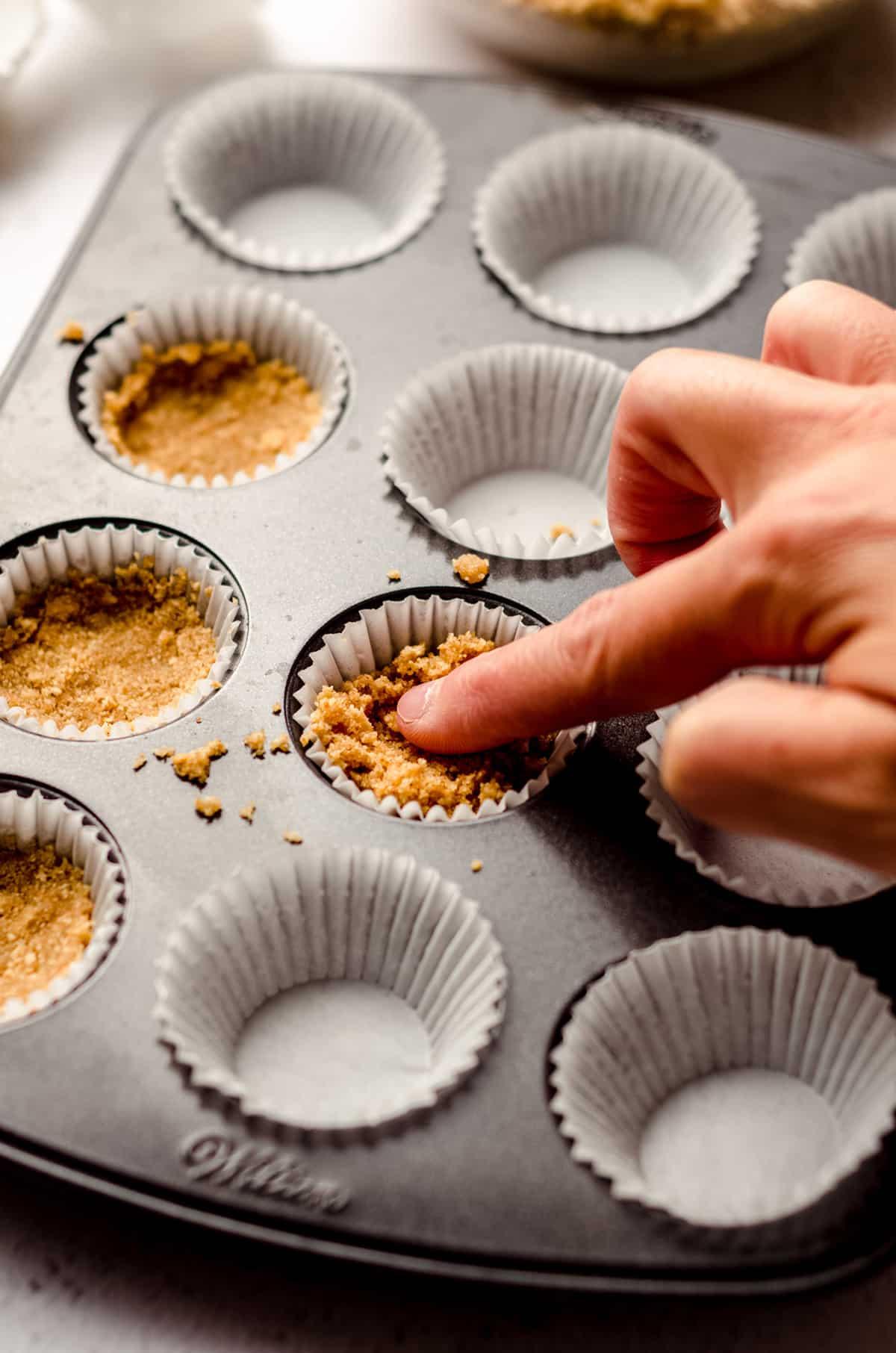 pressing graham cracker crust into the wells of a mini cupcake pan