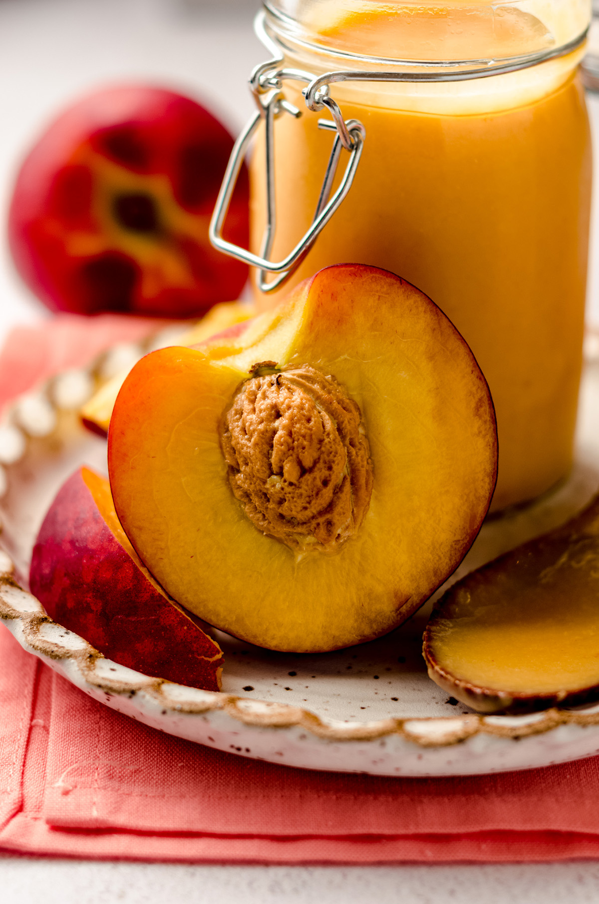 a peach sliced in half with a jar of peach curd in the background