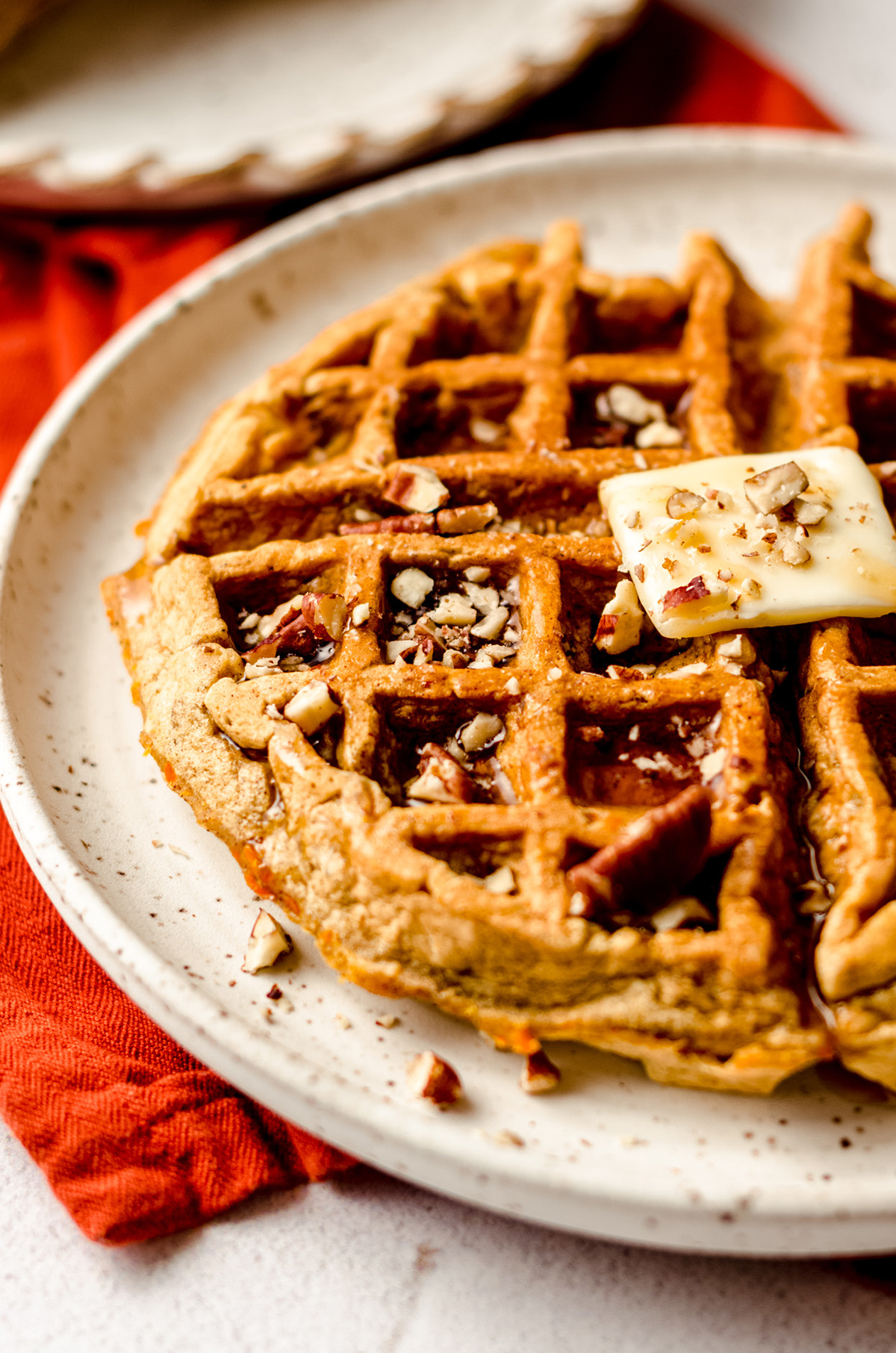 carrot cake waffle with a pat of butter and syrup on it
