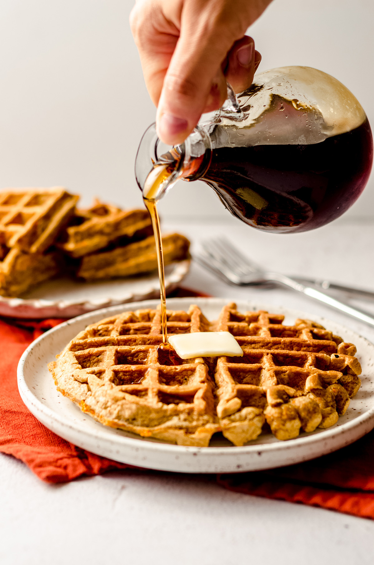 pouring syrup onto carrot cake waffles