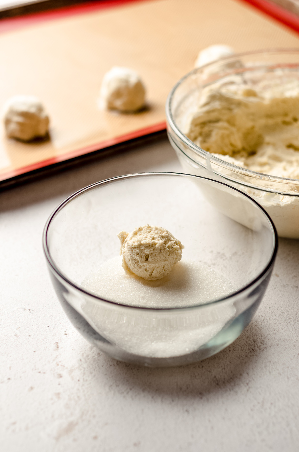 ball of vanilla bean sugar cookie dough in a bowl of sugar