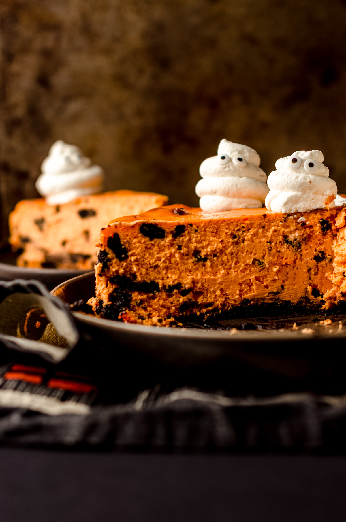 sliced halloween cheesecake with whipped cream ghosts