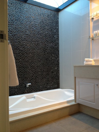 Lovely sunken bath with cool pebble splashback.