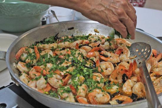 The shrimp team sprinkles parsley over the shrimp.