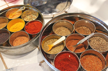 Cooking with Indian spices like turmeric, red pepper, cumin seeds and cardamom.