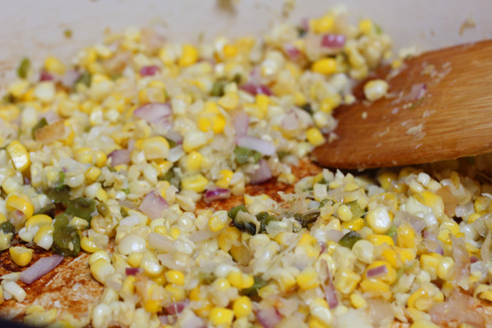 Onion and corn are cooked together in a skillet. Garlic and minced jalapeno are added at the end of cooking.