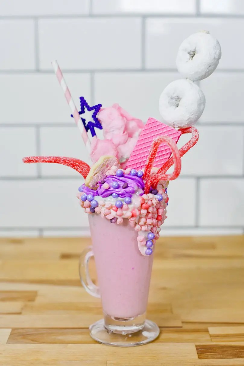 These Epic Royal Crazyshakes are indulgently MAGICAL! A rich, thick strawberry milkshake is topped with a sugaring of sprinkles and candies to make a delicious crazy shake drink fit for aprincess... or a prince. A pretty in pink and purple freak shake!