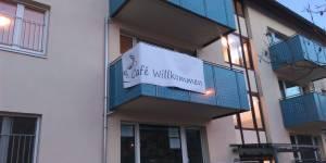 Banner an Balkon = Café Willkommen geöffnet