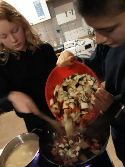 Clara gibt Gemüse in den Wok