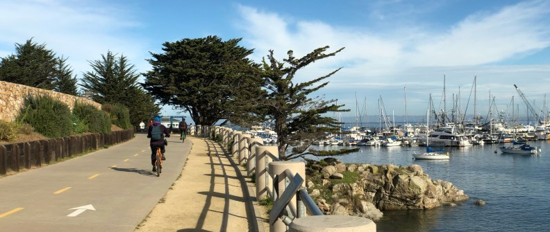 Anamorphic photo of the Monterey walking path along the harbor with bicyclist