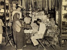 """A couple of GI's consider the pucrhasse of trinkets for the girl friend, harassed by the ever-presetn pleafor """"Baksheesh, Sahib"""", """"You American Rajah"""", """"No food, no money, no poppa""""."""