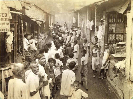 Calcutta's poor from a line to buy keresene at 6 a.m. Each little cubicle may contain a shop and livingquarters for a family ranging possibly from 6 to 12. Sanitary facilities consist of an open street drain.