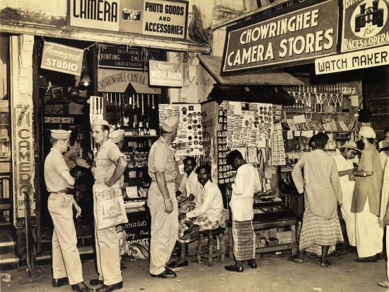Signs notwithstanding, you can't buy cameras, binoculars, photo goods or accessories here, but the stock does include anything from a Legion of Merit ribbon to an ivory necklace, brass ashtray, ladies evening bag, shoestrings or napkin rings. Typical shoppers ponder the situation.