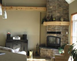 RSF Delta huge glass wood fireplace stoned in a corner with wood beam mantle