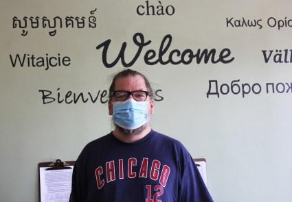 Photo of Alex in front of the Friendship Center's welcome wall