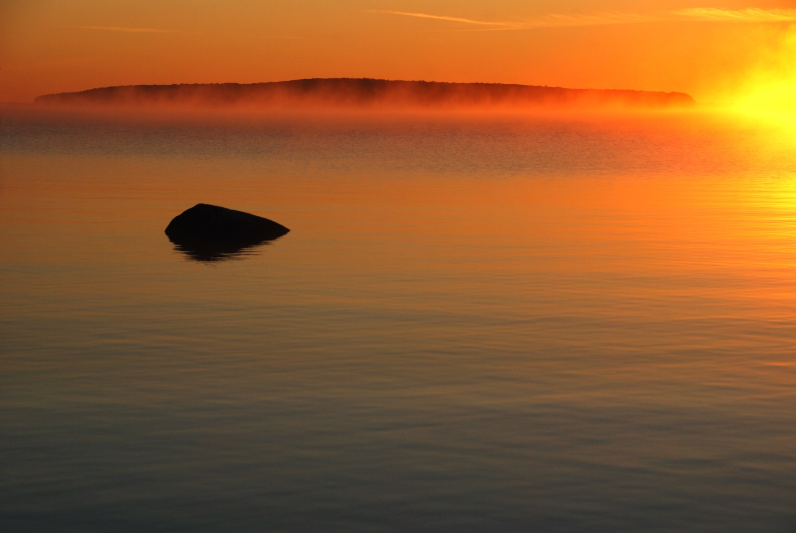 Lone rock in foreground, island in the mist