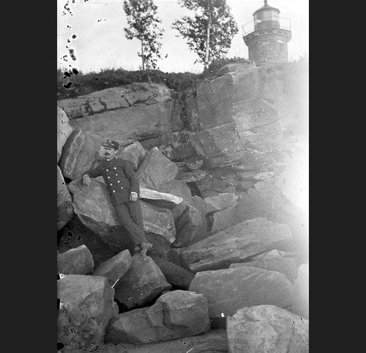 Emmanuel Luick in his keeper's uniform on the rocks below the Sand Island Light.