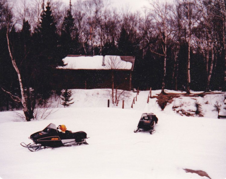 park snowmobiles parked near the old Presque Isle ranger cabin at Stockton Island